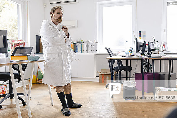 Businessman wearing bathrobe in office holding cup
