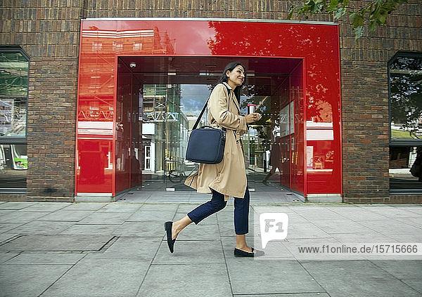 Junge Geschäftsfrau mit wiederverwendbarer Kaffeetasse  Spaziergang in der Stadt