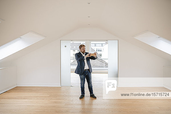 Estate agent standing in empty apartement taking pictures