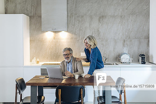 Mature man with wife using laptop on kitchen table at home