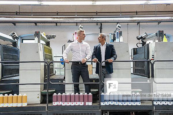 Zwei Geschäftsleute im Gespräch in einer Druckerei