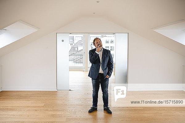 Businessman standing in empty apartement looking around