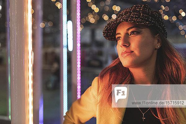 Porträt einer Frau mit Lichtern in der Stadt bei Nacht