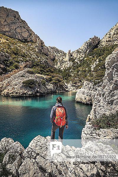 Frankreich  Côte d'Azur  Calanques-Nationalpark  Frau mit Rucksack  Blick auf Kreidefelsen und Buchten