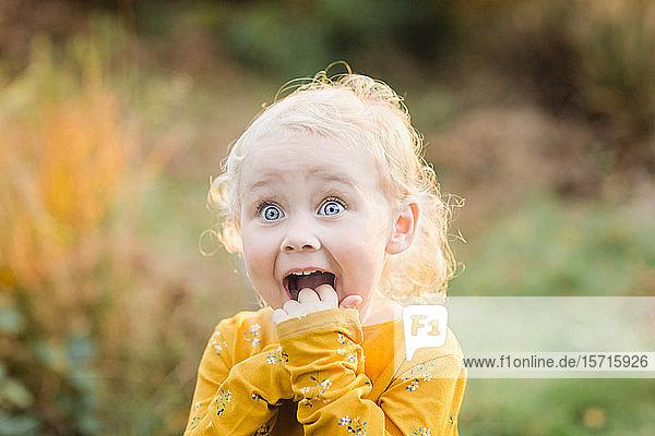 Bildnis eines blonden Kleinkindes mit blauen Augen  die lustige Gesichter ziehen