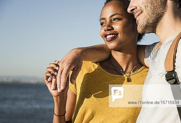 Liebevolles junges Paar  das sich an der Uferpromenade umarmt  Lissabon  Portugal