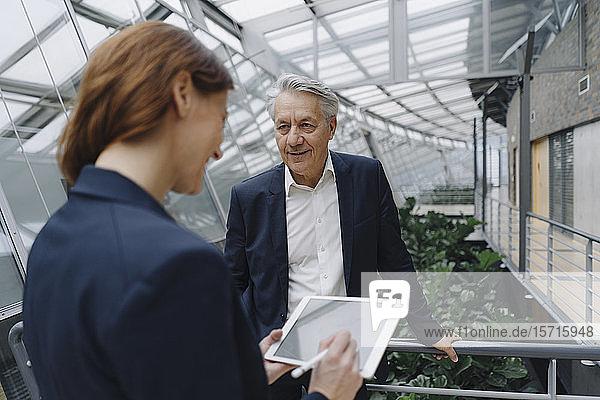 Lächelnder Geschäftsmann und Geschäftsfrau mit Tablette in modernem Bürogebäude