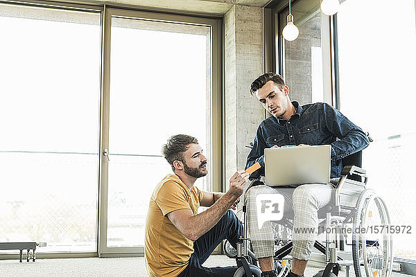 Young businessman in wheelchair and colleague using laptop in office