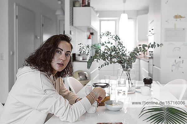 Porträt einer Frau  die am Küchentisch sitzt und Tee trinkt