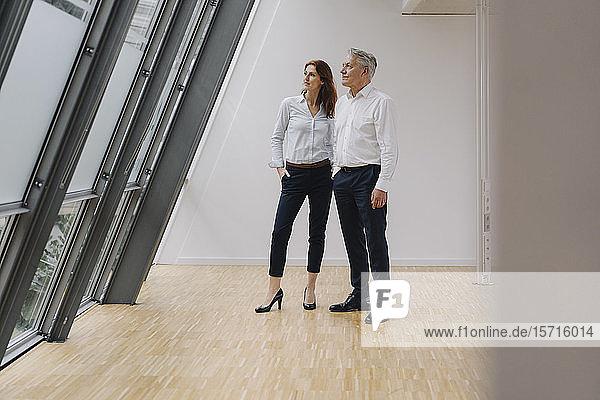 Geschäftsmann und Geschäftsfrau im Amt  die aus dem Fenster schauen