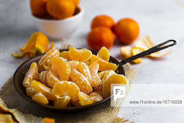 Heap of freshly peeled mandarines on frying pan