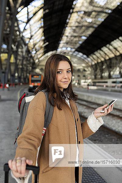 Porträt einer lächelnden jungen Frau mit Handy in der Hand am Bahnhof