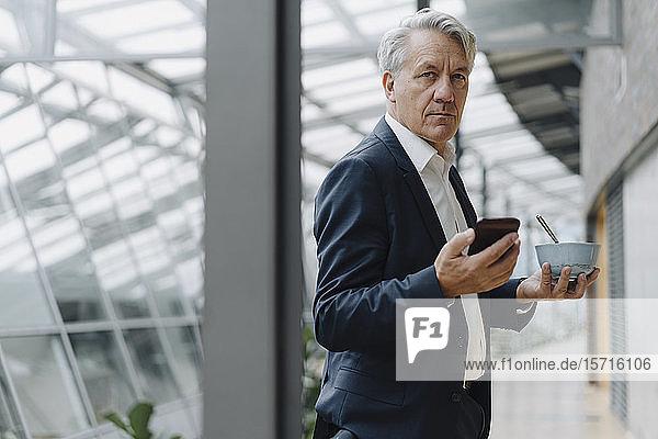 Leitender Geschäftsmann mit Smartphone und Müsli-Schüssel im Amt