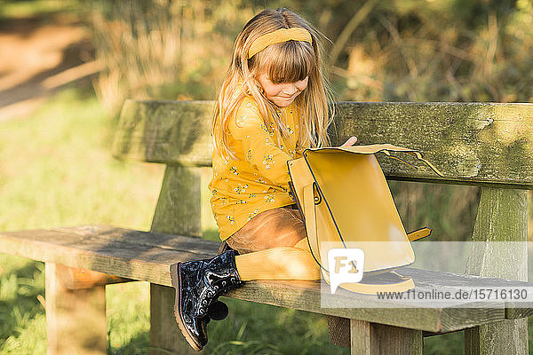Kleines blondes  gelb gekleidetes Mädchen auf Gartenbank sitzend mit Ledertasche