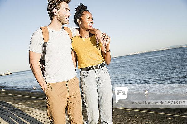 Glückliches junges Paar beim Spaziergang am Wasser  Lissabon  Portugal