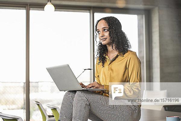 Junge Geschäftsfrau sitzt mit Laptop auf dem Schreibtisch im Büro