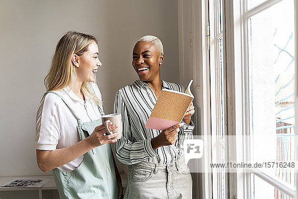 Two happy women with notebook and cup of coffee at the window