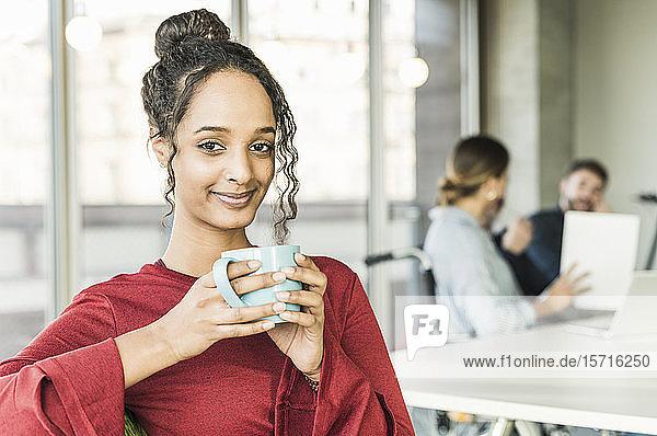 Porträt einer lächelnden jungen Geschäftsfrau bei einer Kaffeepause während einer Besprechung im Büro