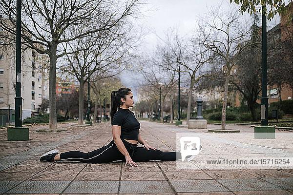 Junge Frau in schwarzer Sportkleidung beim Spagat auf dem Bürgersteig