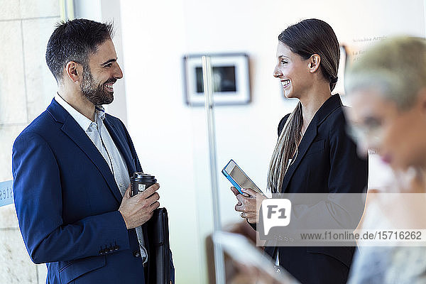 Lächelnde Geschäftsleute sprechen im Büro