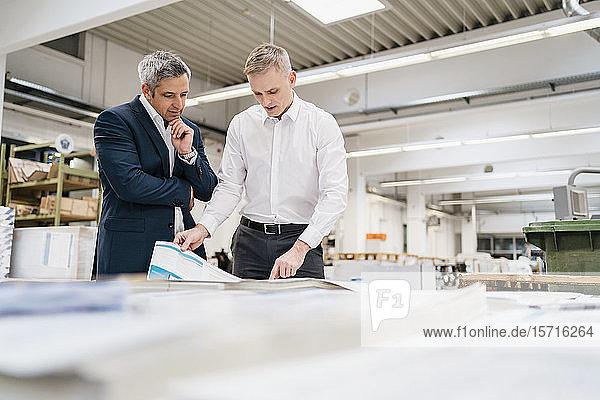 Zwei Geschäftsleute diskutieren in einer Fabrik über Papier