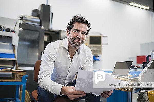 Porträt eines selbstbewussten Geschäftsmannes mit Papieren in einer Fabrik