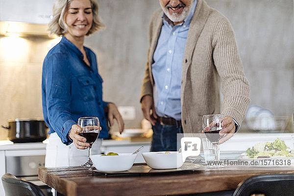 Reifes Paar  das während des Abendessens in der heimischen Küche Weingläser hebt Reifes Paar, das während des Abendessens in der heimischen Küche Weingläser hebt