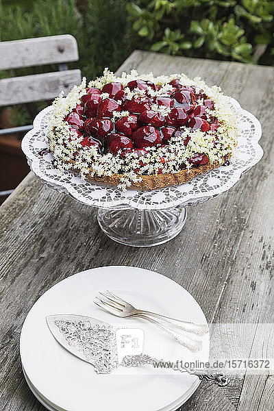 Cake stand with homemade strawberry cake decorated with elderflowers