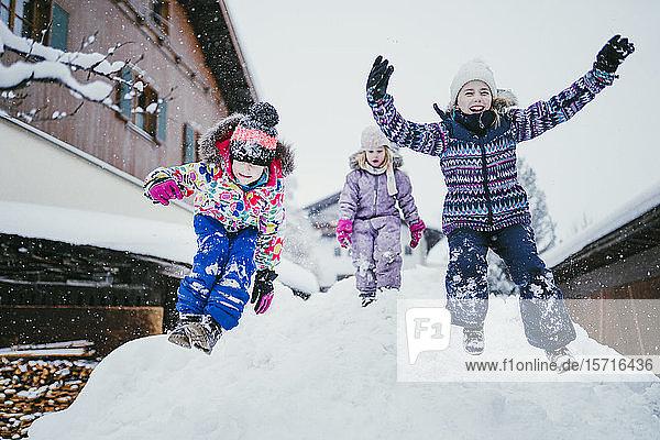Drei Kinder spielen im Schnee  Jochberg  Österreich