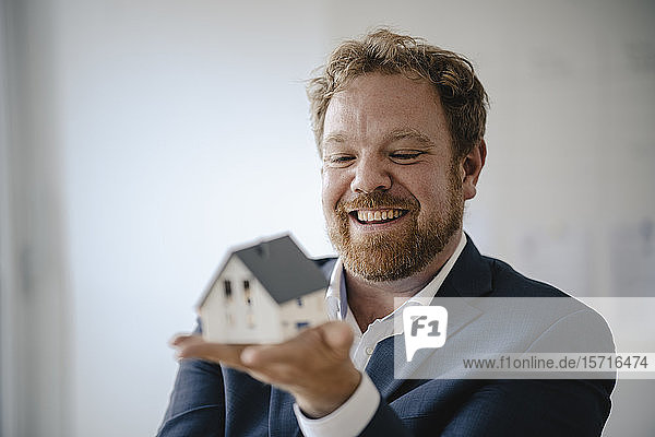 Happy businessman holding model house in office