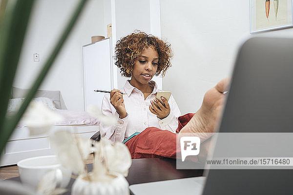 Entspannte junge Frau sitzt zu Hause am Tisch und benutzt ein Smartphone