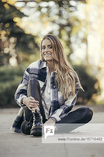 Porträt einer lächelnden jungen Frau  die im Freien auf dem Boden sitzt