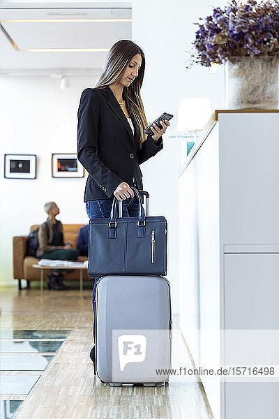 Geschäftsfrauen überprüfen ihr Smartphone an der Rezeption