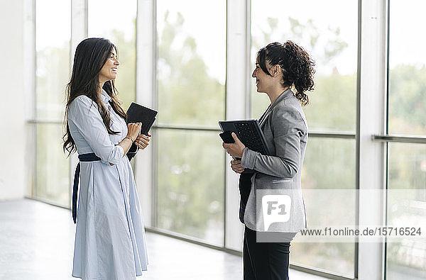 Zwei glückliche Geschäftsfrauen im Gespräch am Fenster