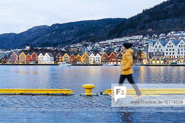 Frau in gelber Jacke bei einem Hafenspaziergang in Bergen  Norwegen