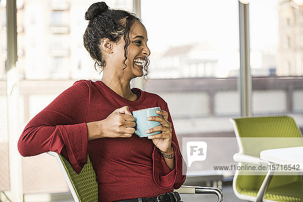 Happy young businesswoman having a coffee break in office