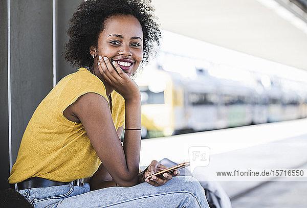 Porträt einer lächelnden jungen Frau mit Handy auf dem Bahnhof