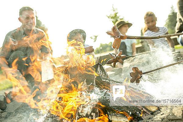 Kinder braten Würstchen am Lagerfeuer an Stöcken