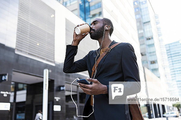 Young businessman with earphones and smartphone drinking coffee to go outdoors