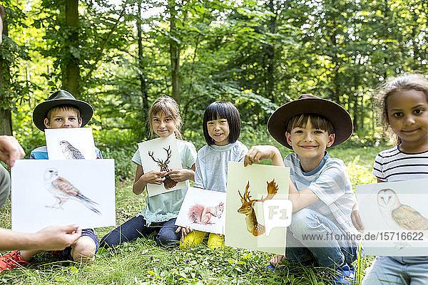 Schulkinder machen Naturstudien  halten Bilder von Tieren
