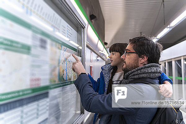 Father and daughter looking on map at metro station