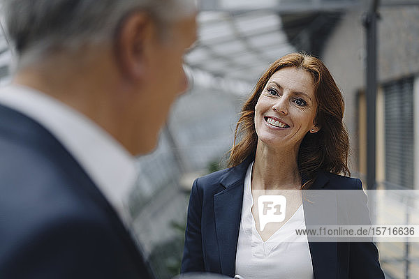 Porträt einer lächelnden Geschäftsfrau im Gespräch mit einem Geschäftsmann im Amt
