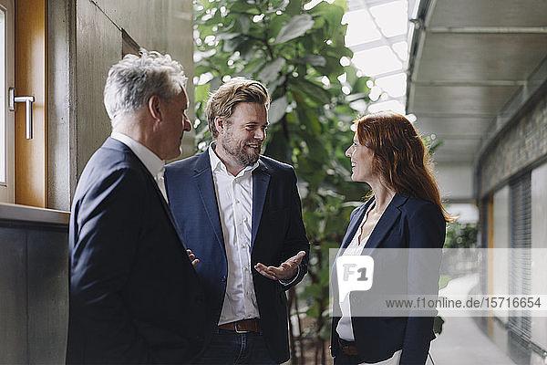 Lächelnde Geschäftsleute im Gespräch in einem modernen Bürogebäude
