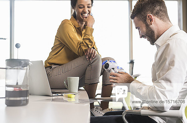 Young businessman with colleague in office holding robot