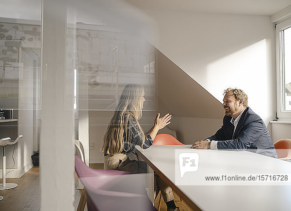 Businessman and businesswoman talking at conference table in office