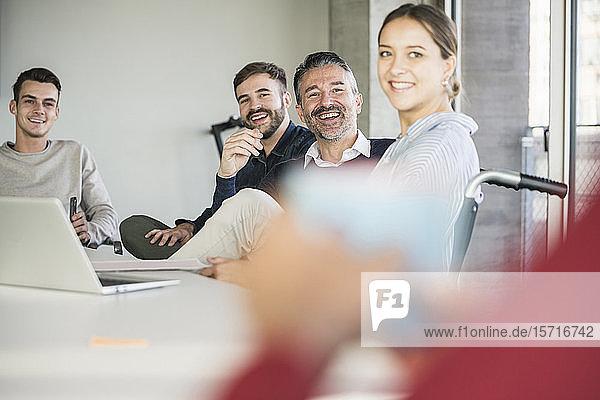 Glückliche Geschäftsleute während einer Besprechung im Amt