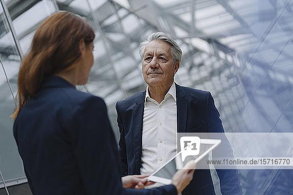 Geschäftsmann und Geschäftsfrau mit Tablett in modernem Bürogebäude