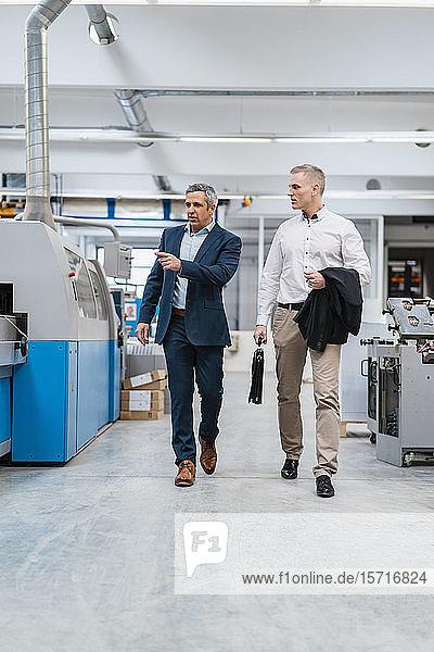Zwei Geschäftsleute gehen und reden in einer Fabrik