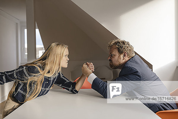 Geschäftsmann und Geschäftsfrau im Armdrücken im Amt