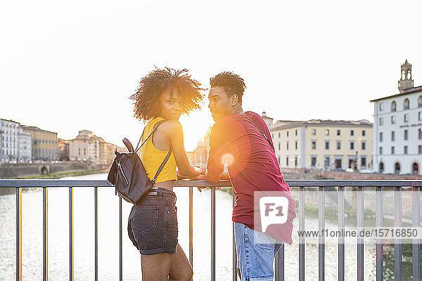 Junges Touristenpaar steht bei Sonnenuntergang auf einer Brücke über dem Arno  Florenz  Italien